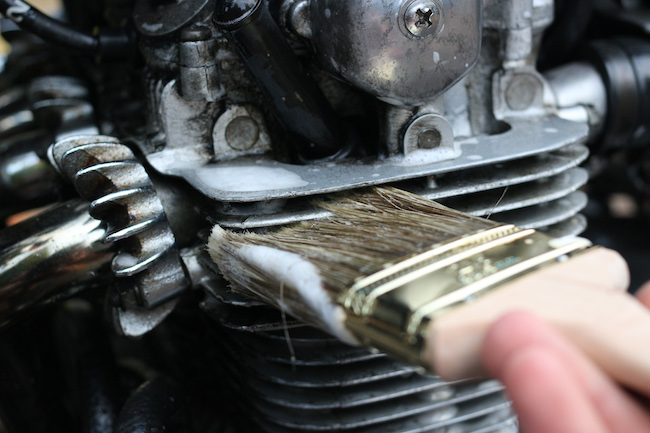 Cleaning the engine with brush.