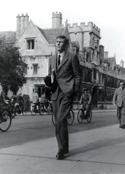 A vintage formal dressed man walking in the street with one hand in pocket.