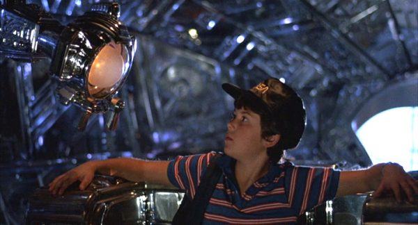 "Scene from the movie "" Flight of Navigator"" in which boy is looking at a machine."