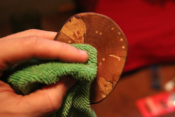 Wiping wooden coaster with microfiber cloth.