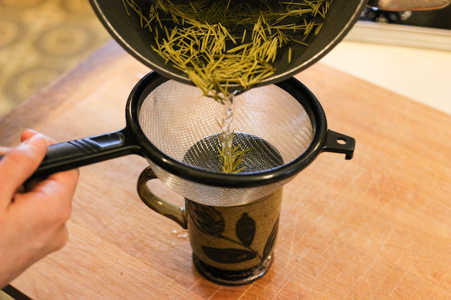 Filtering Douglas fir after boiling in water with strainer.