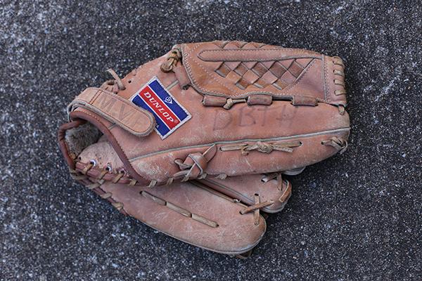 Dirty baseball glove on the floor.