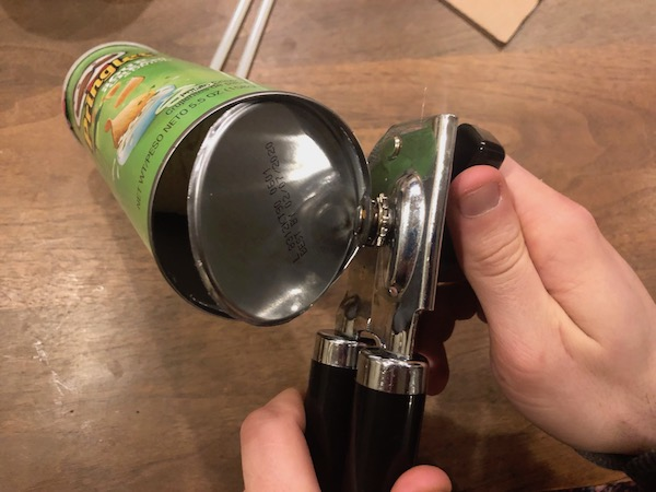 Removing the bottom of Pringles can with can opener.