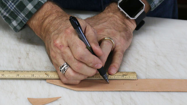 Measuring the leather strip by scale and pen.
