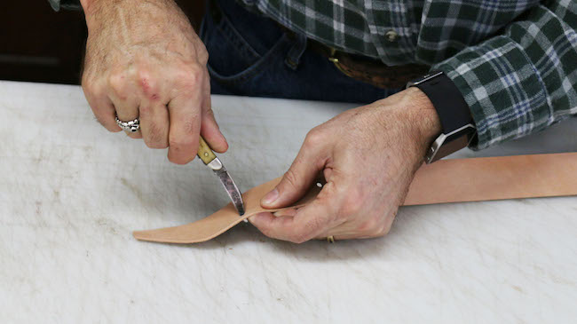 Cutting the leather strip by a knife.