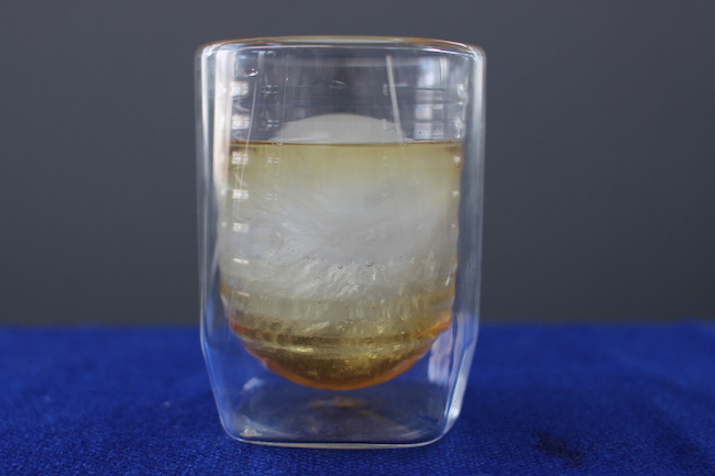 Aged & Ore Duo Glass contains whiskey and ice.
