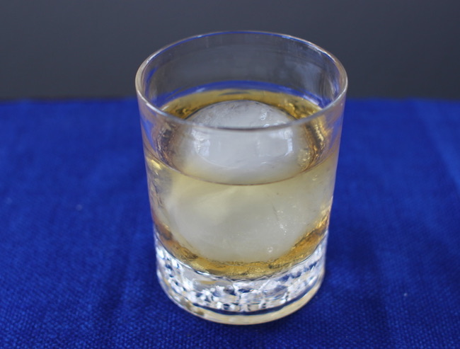 """Classic, Hefty """"Rocks"""" glass with whisky and ice."""