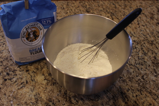 Whisking flour, salt, and yeast together in a bowl.