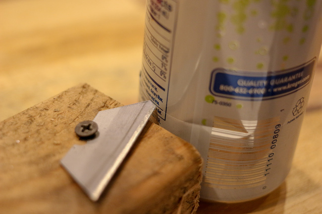 Cut base of can along with wooden box and a nail drilled in it.