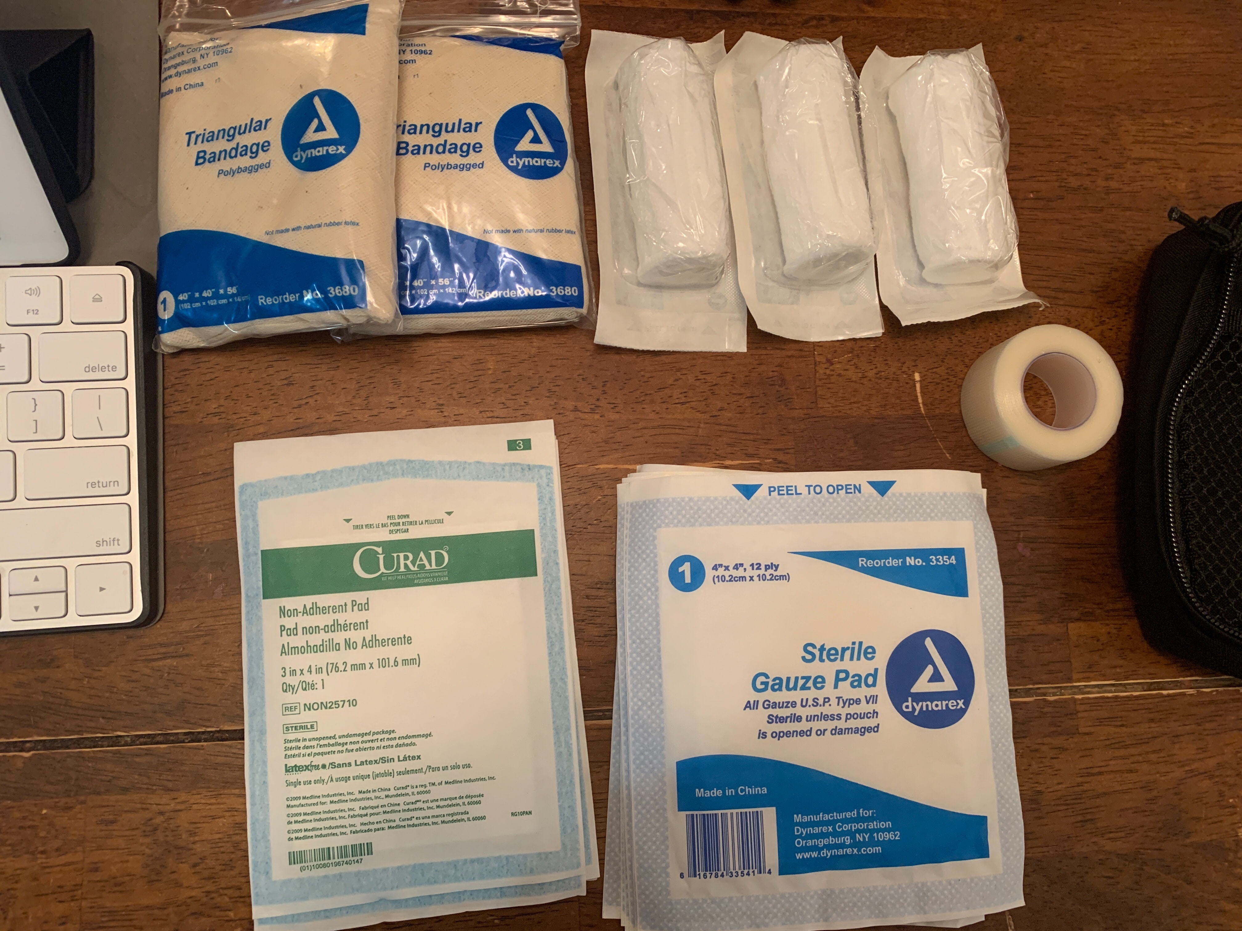 Pair of triangular bandage, gauze pad, tape, a set of nonstick dressings and rolled gauze being presented.