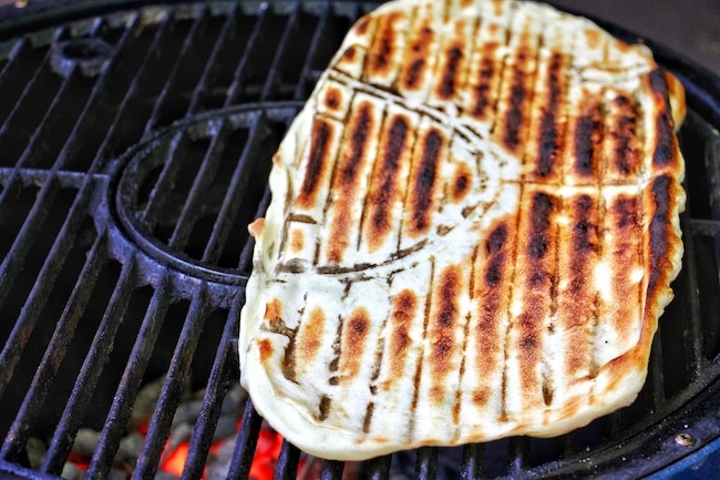Cooked side of pizza dough on grill.