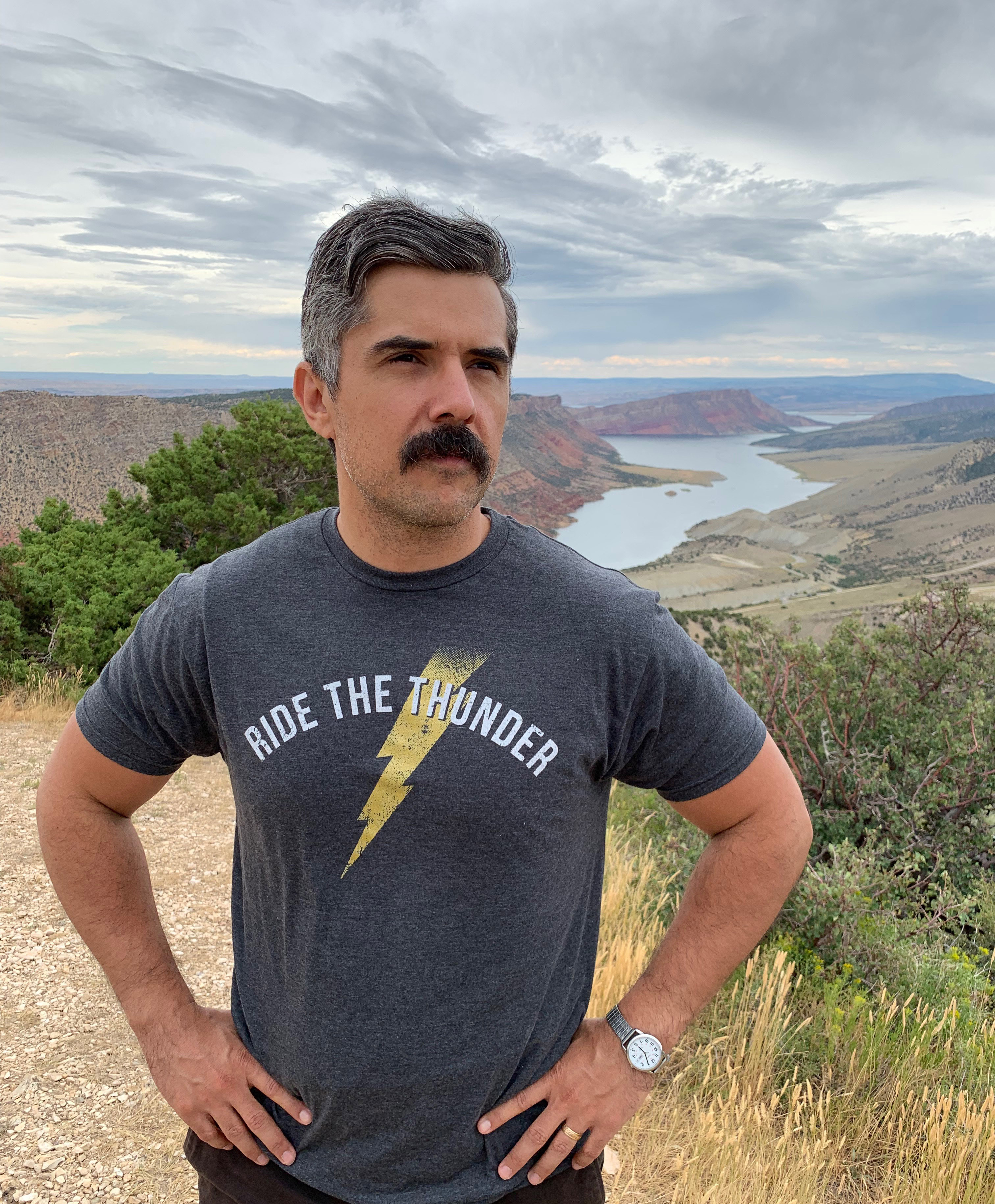 Man standing on a mountain wearing Ride The Thunder shirt.