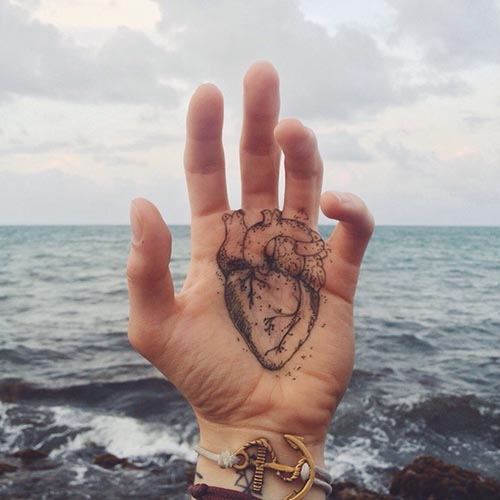 Man's hand with heart drawing tattoo on it.