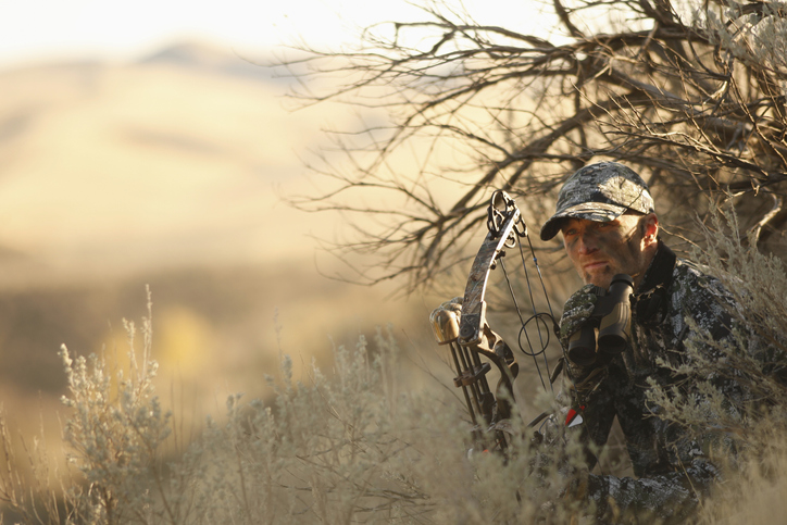 Bowhunter in camouflage crouching in field.