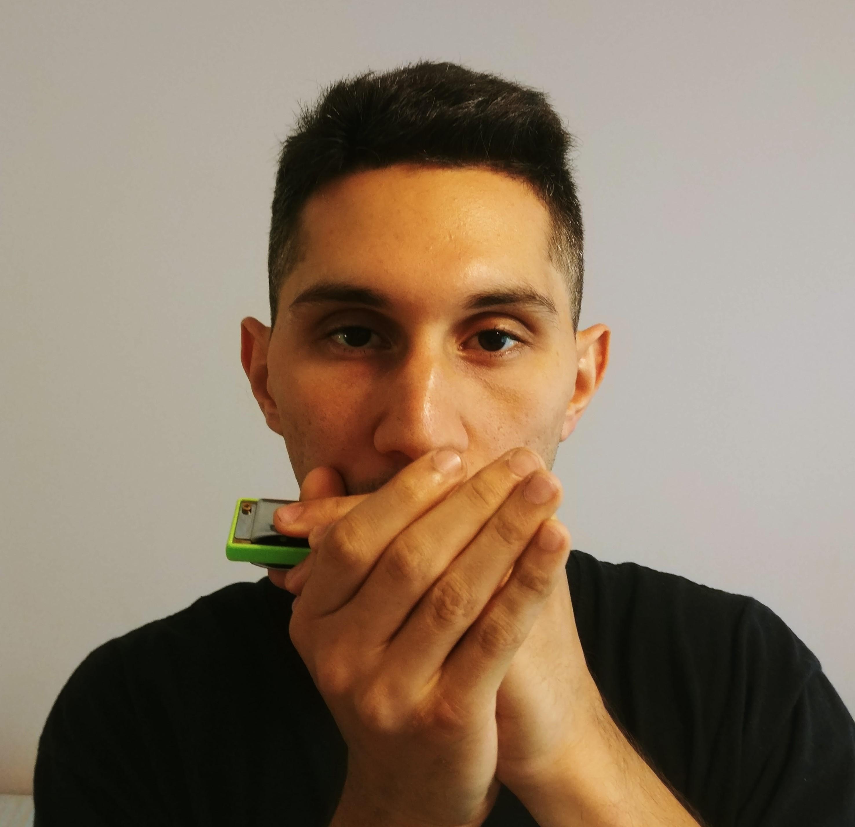 A boy holding the harmonica.