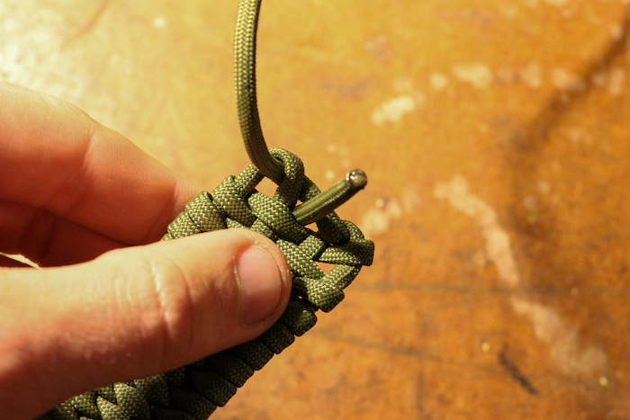 Step 8: End your weave by passing the paracord through the hole in the center of the pouch.