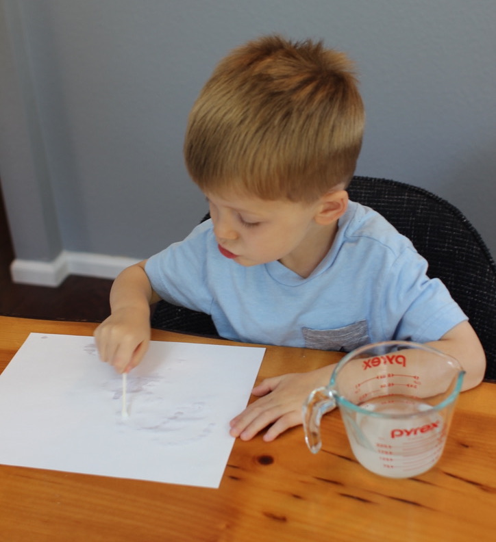 Kid is drawing with invisible ink.