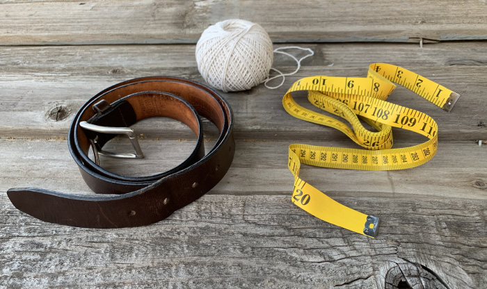 Belt, measuring tape and thread displayed on table.