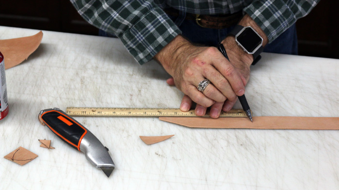 Measurement of leather strip with the help of ruler is shown.