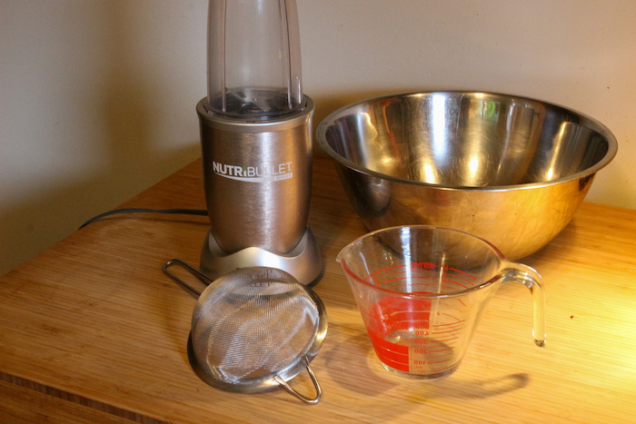 Blender, Mesh strainer, Mixing bowl and Measuring cup being displayed on the table.