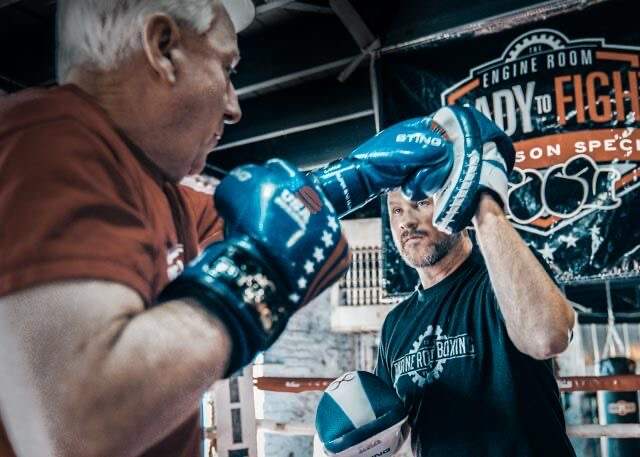 Men having boxing practice with each other.