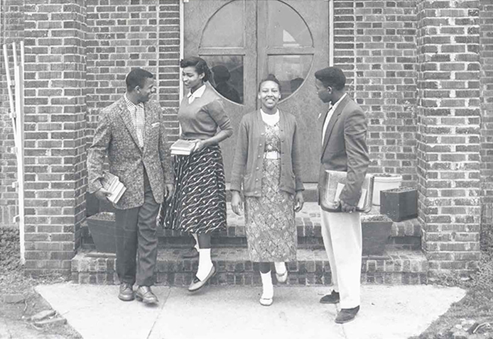 Students having conversation while holding books outside building.