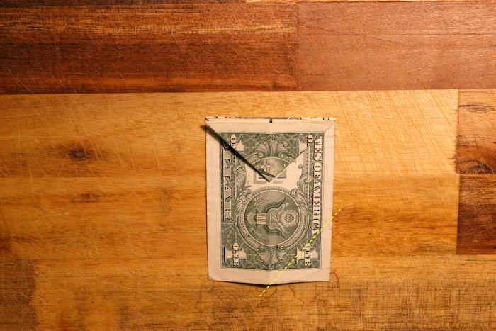 Fold dollar bill from marked line.