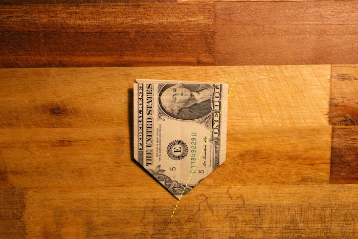 Flip the bill over so that Washington's head is up. Fold the bottom right flap up until it meets the center of the bill. It should finally feel a bit like you're making a paper airplane's wings. Repeat with the other side.