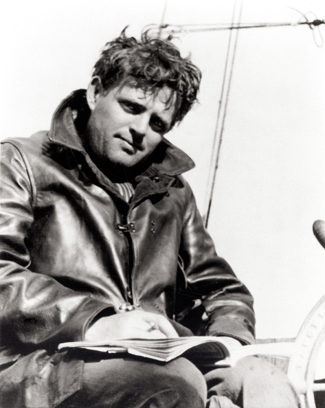 Jack London with a book on his lap while sitting on a yacht.