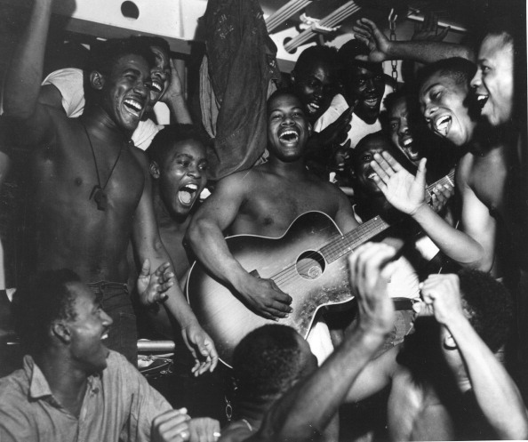 Vantage Niger playing guitar and others are singing and laughing.