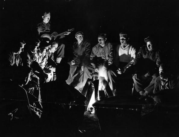 Vintage men singing around a campfire.