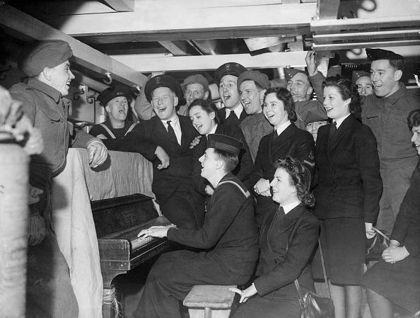 A group of vintage singing and a guy paying piano.