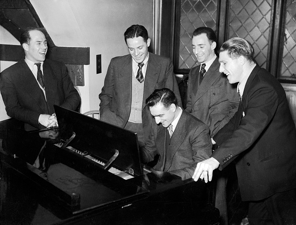 A vantage group looking at a man who is playing piano.