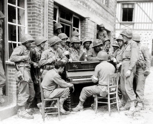 Vantage group of soldiers listening to piano.