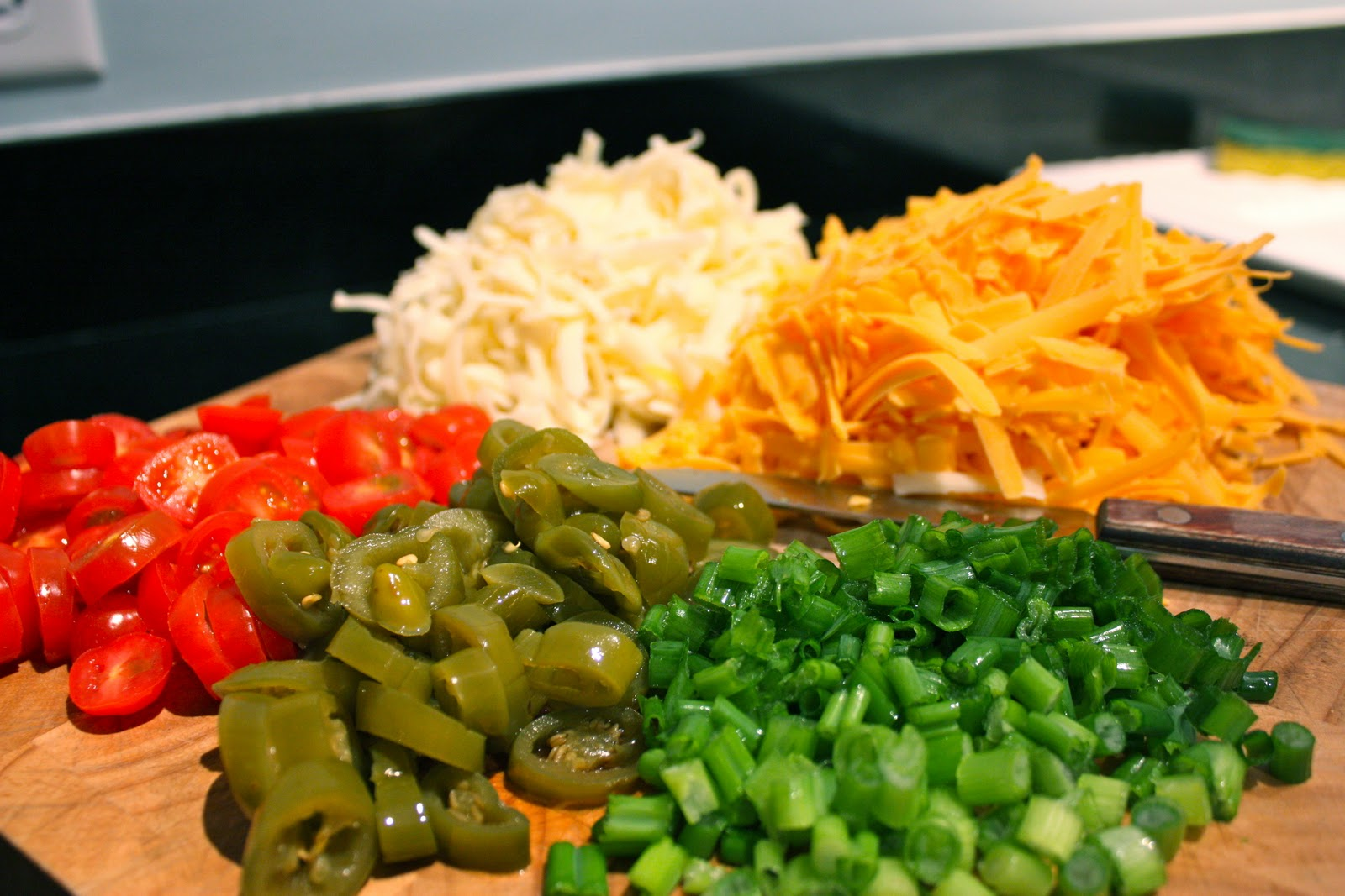 Cheese and different vegetables on chopping board.