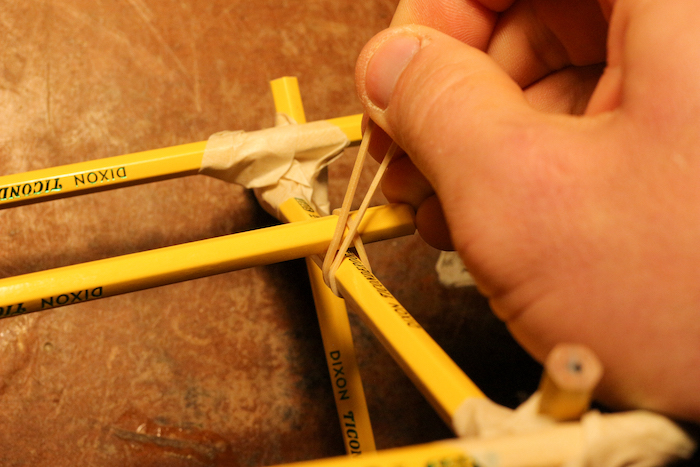 Attaching a pencil halfway up on the other side of the supports by rubber bands.