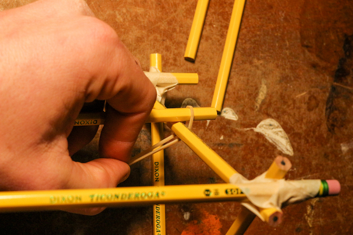 Attaching a pencil halfway up one side of the supports using rubber bands.