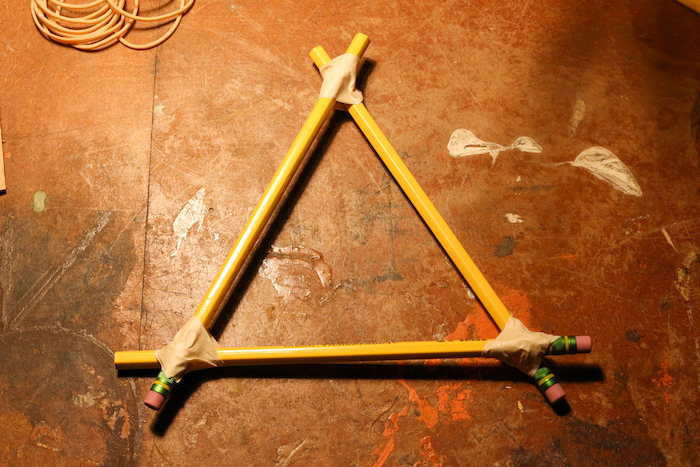 Pencils are attached with each other in a triangular shape with the help of tape.