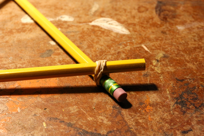 Two pencils attached with rubber band at one end.