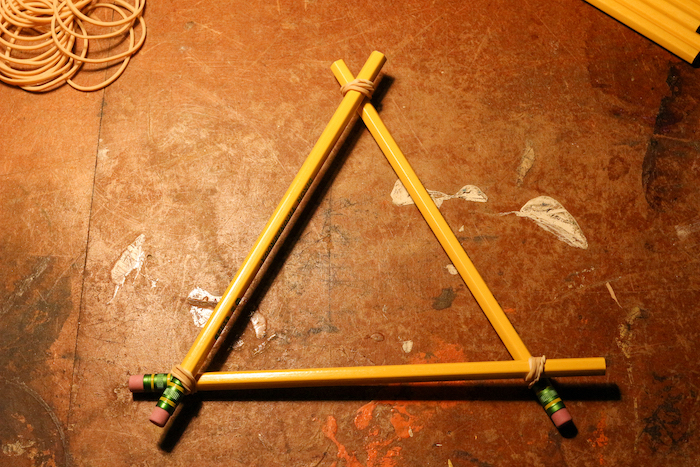 Attaching pencils with the help of rubber bands to make them triangular shaped.