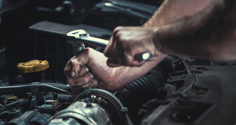 Mechanic tightening the screw of car.