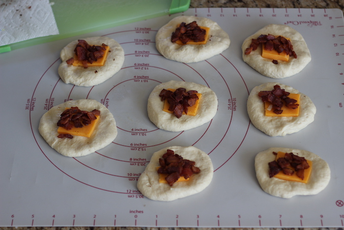 Bacon and cheese being placed on dough.