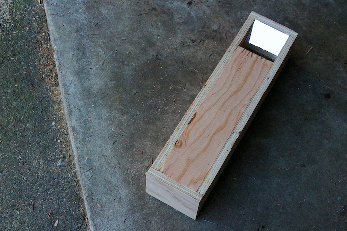 A wooden box with a mirror placed on ground.