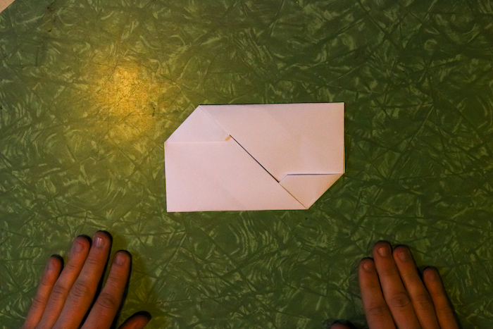 Tucked corners of paper with hands.