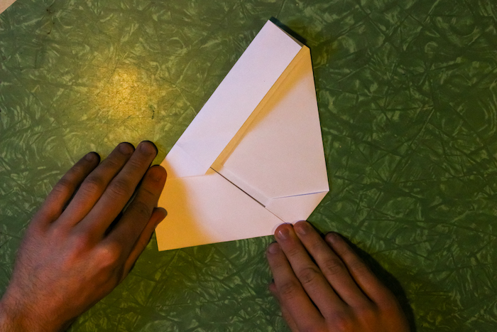 Tucking the corner of the paper under with the help of hands.