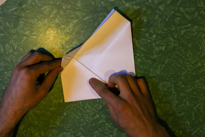 Lifting the long flap of the paper by hand.