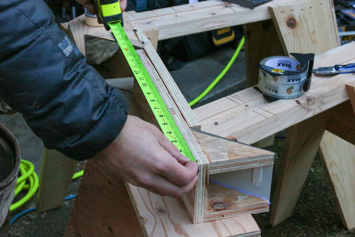 Side of plywood is being measured.