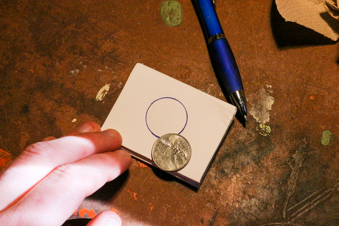 Making quarter on paper with the help of pen and quarter.