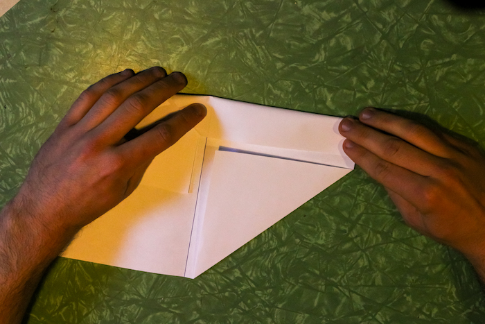 Folding one side along with adjacent sides of paper.