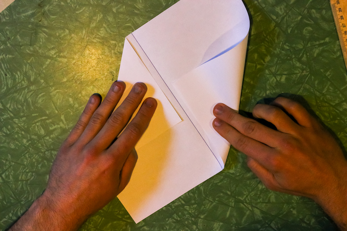 Folding adjacent corners of paper by hands.